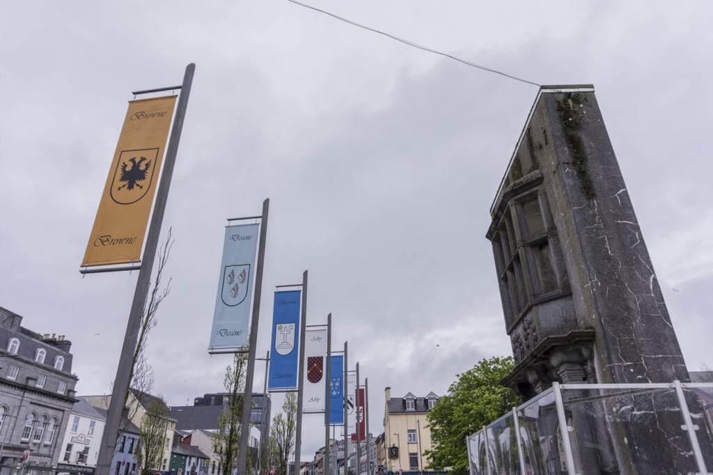 """Eyre Square con """"The Browne doorway"""" y algunas de las banderas de las tribus de Galway"""